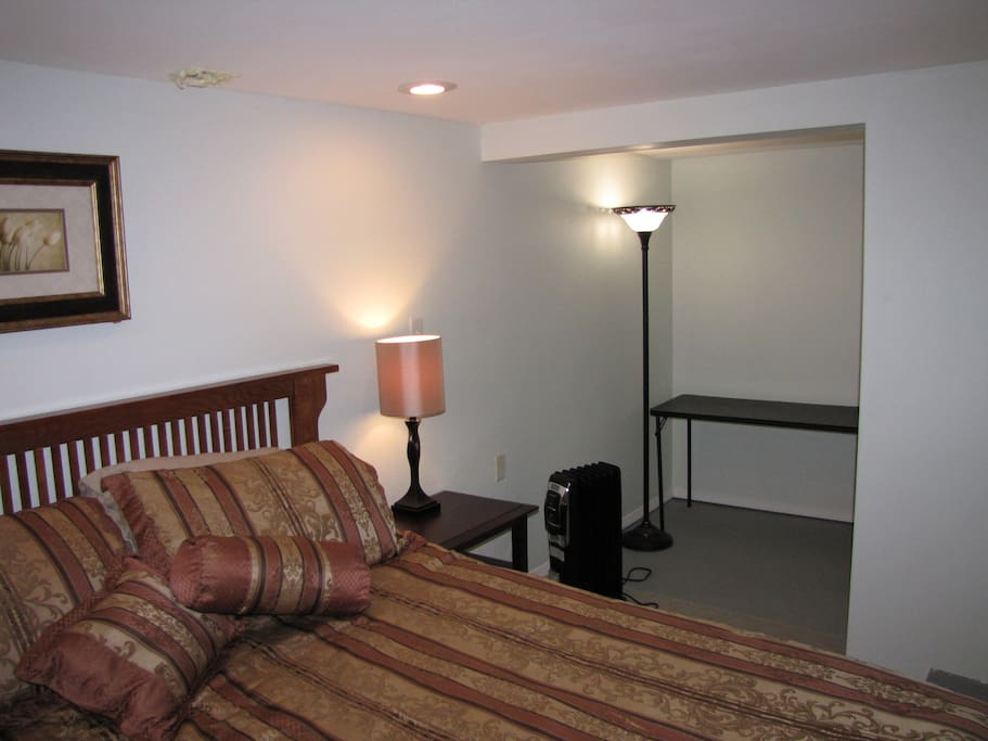 Bed with storage area and folding table for desk.  To the right of the table is a closet.