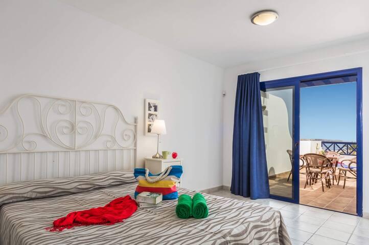 Dormitorio principal con cama de matrimonio, baño ensuite y terraza. Se encuentra en la primera Planta