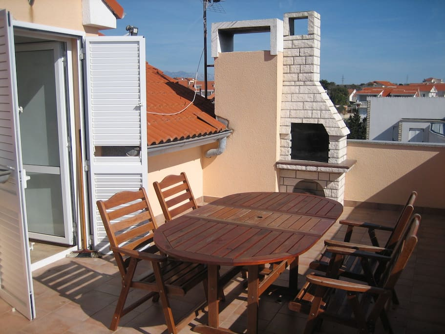 Large balcony with table, chairs and BBQ