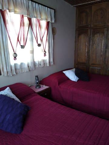 Segunda recámara (2 camas matrimoniales) con closet y 2 ventanas con vista a los jardines y vista panorámica.