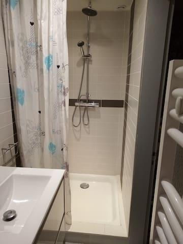 La salle de bain privative accessible par la chambre 1 : douche, lavabo et sèche-serviette.