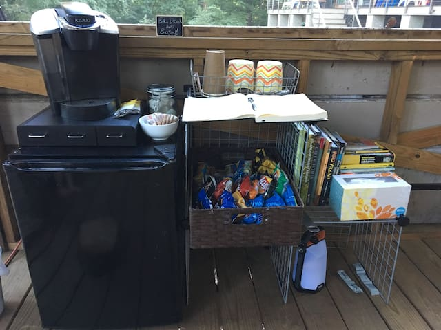 The treehouse comes with a small fridge, Keurig coffee maker (which also makes tea, hot chocolate, and hot cider--all available in the pull-out drawers beneath the Keurig), and a basket of snacks to enjoy. Plus, see all those books behind the tissue box? We've cultivated a collection of true treasures.