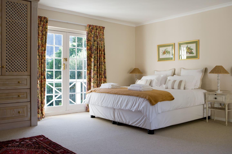 Main bedroom with en-suite bathroom, balcony, built-in cupboards and carpeted floors
