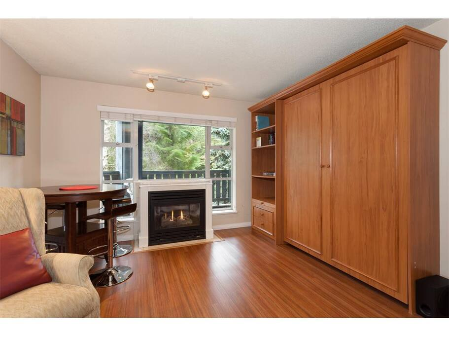 A hidden murphy bed is located inside the large wooden closet.