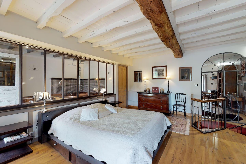 Chambre avec verrière donnant sur la salle de bain
