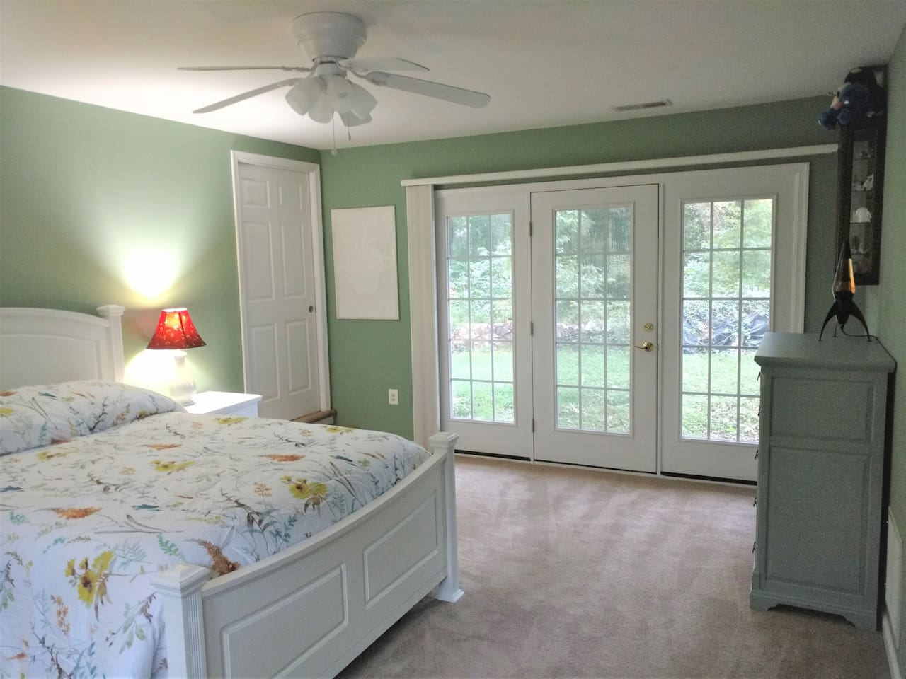 Spacious master bedroom with queen bed. Lots of natural light. Honeycomb shades for both the French doors and the windows on the opposite wall.