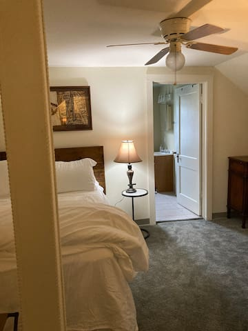 Upstairs huge bedroom with bathroom that has shower, toilet and sink