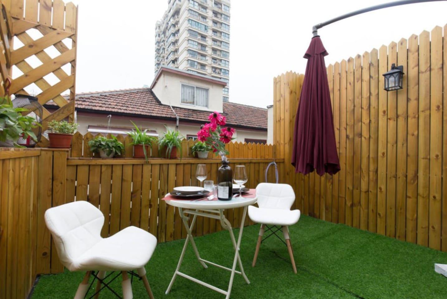 带有餐桌餐椅还有遮阳伞的花园露台