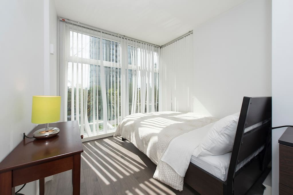 The full-length windows in this bedroom allow for plenty of natural light to come in