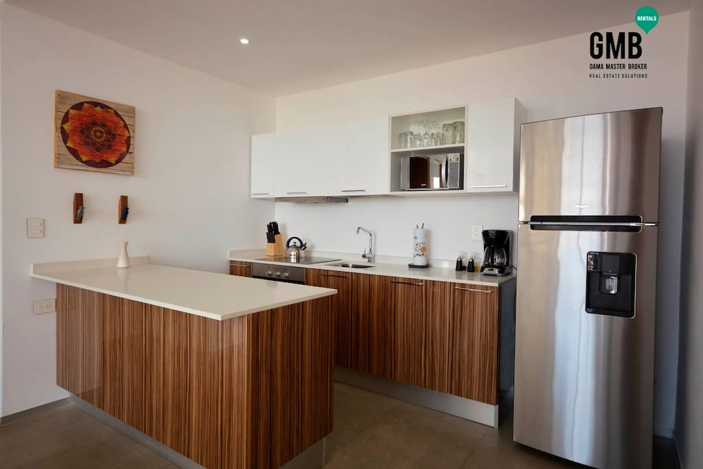 Completly Kitchen with a Kitchen Bar.