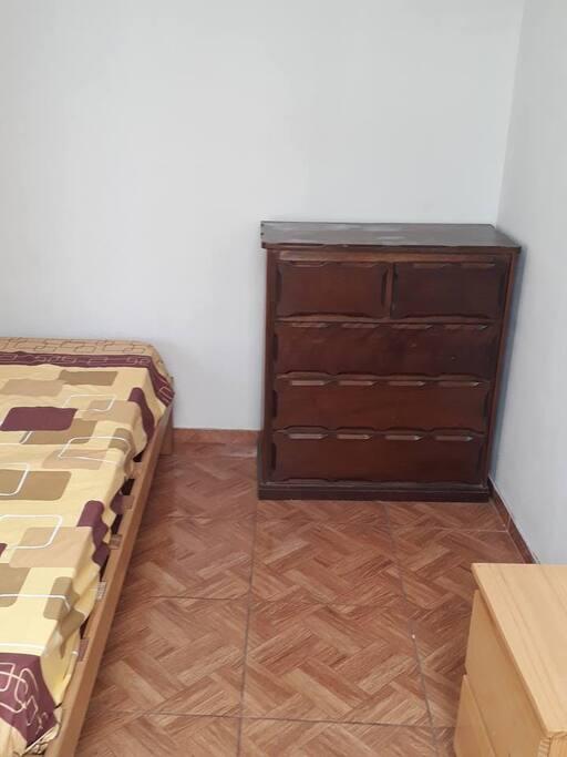 Habitación con cama de 1 plaza, velador, cómoda y espacio para colgar ropa. Se ubica en un 4to piso.