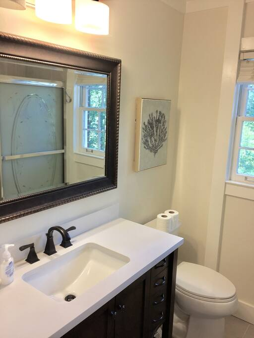 Bathroom w/ framed mirror and Marble Counter! This bathroom is shared with one other bed room.