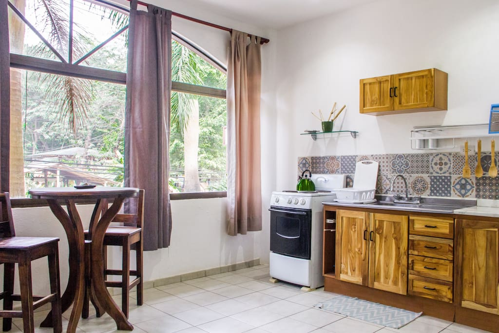 fully equipped kitchenette with full sized fridge. stools and table