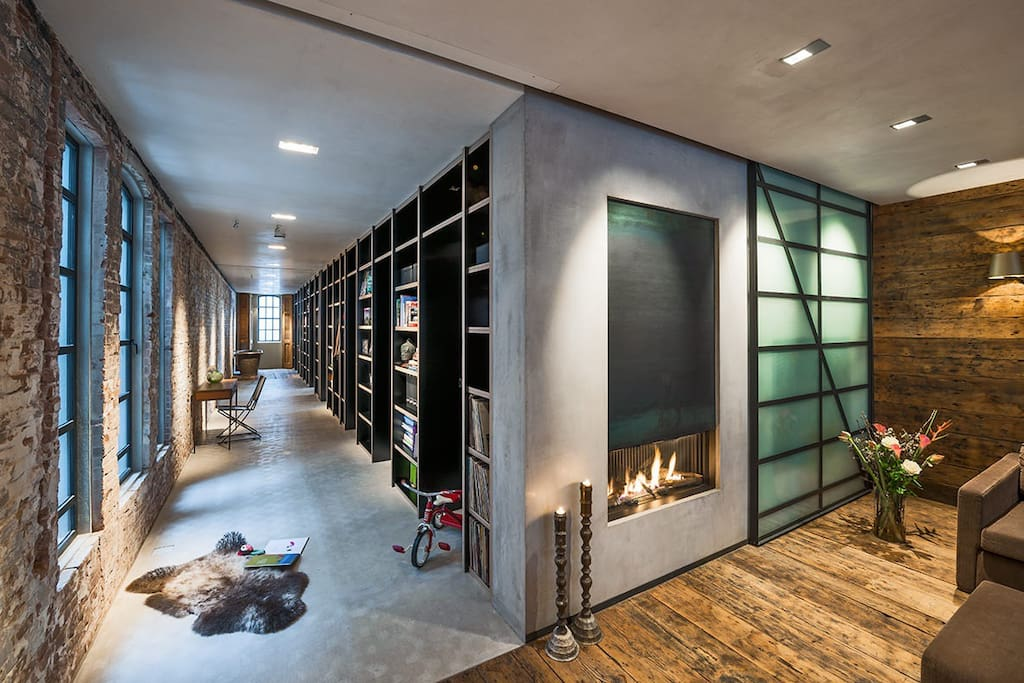 Wide hall way with a 16 meter long book shelf, with entrances to bed and bathrooms