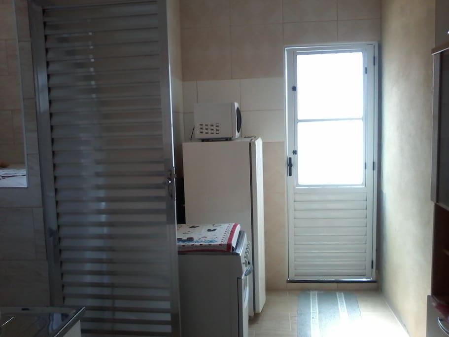 Cozinha completa com fogão, geladeira, microondas, fogão, pia, armário, utensílios e produtos de limpeza.
