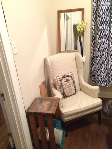 A cozy chair is great for reading or tying a shoe. Extra blankets are tucked in a vintage fruit crate.