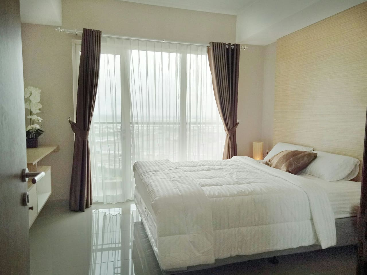 A cozy Luxury  Modern Bedroom  equipped  byTV cable  with large window  city view