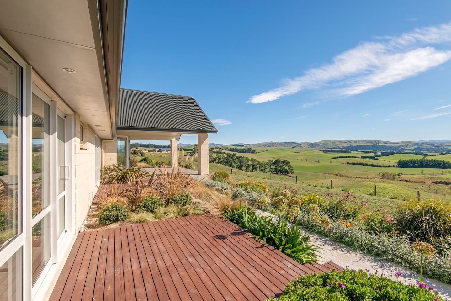 The view from the house is of the rolling pasture land leading up to the hills and mountains in the distance.  Each room has sliding doors that open out onto a deck.  Kowhai's deck has a view of the garden and some distant mountains.