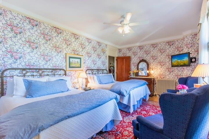 This Best Friends room is a very feminine room with two brass queen beds and en suite bathroom and TV on the second floor. It;s the only room in the mansion with 2 beds.