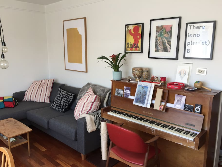 Cozy sofa with blankets, art on the walls and a piano.