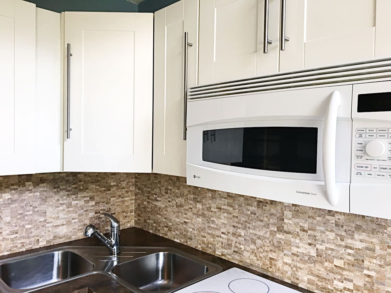 Kitchen with double sink, glass top range, and convection oven.