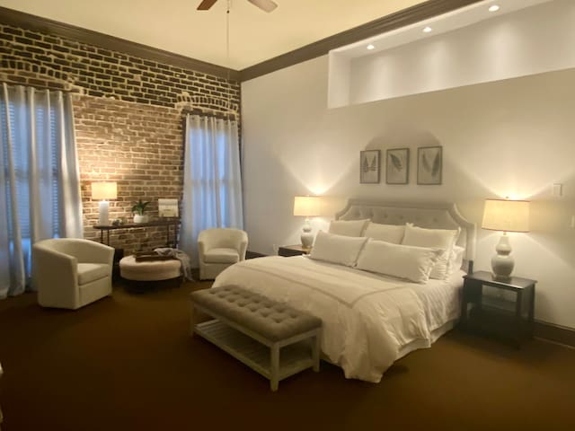 Huge Bedroom that is Beautifully decorated. Original brick wall with 20 ft. ceilings. Spacious king size bed with plush linens. The bedroom has a flatscreen TV mounted on the wall across from the bed.