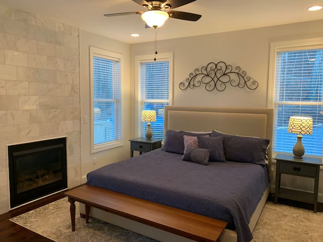 Master bedroom on main floor with King size bed and fireplace.