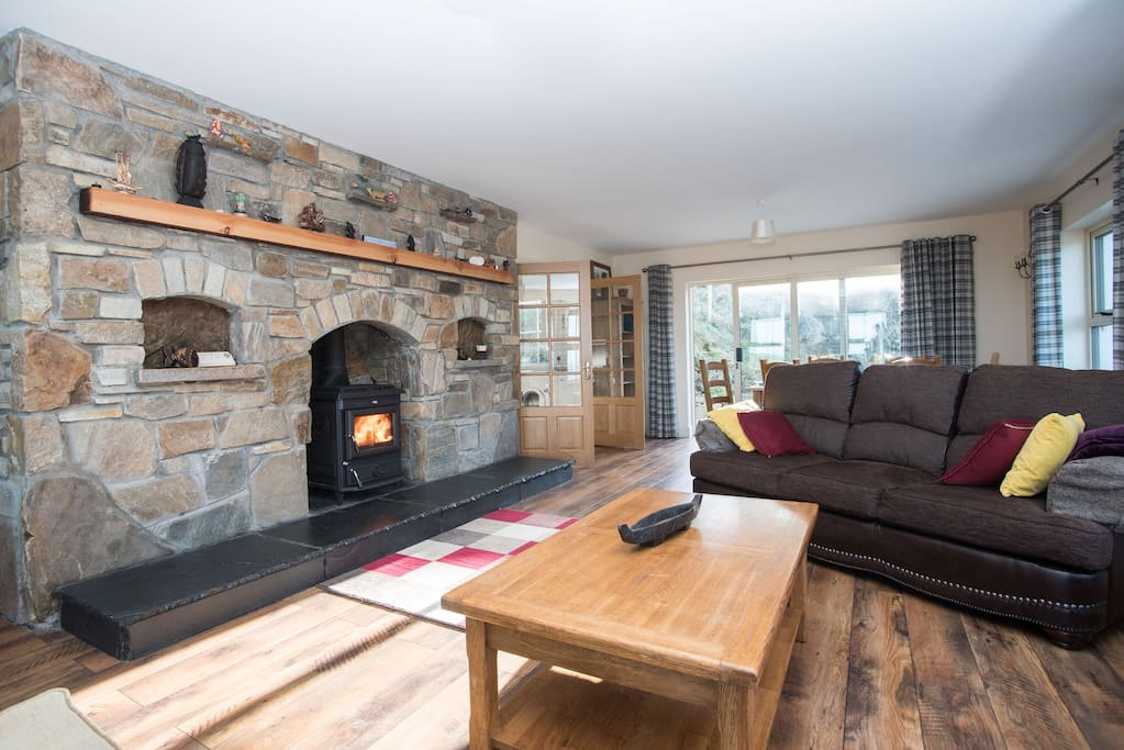 Sitting room with Stonework fireplace and stove.