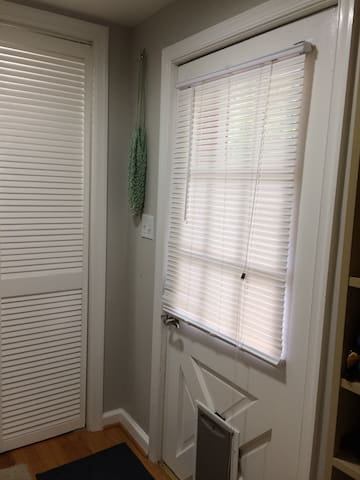 Inside coded entry with coat closet behind louvered doors