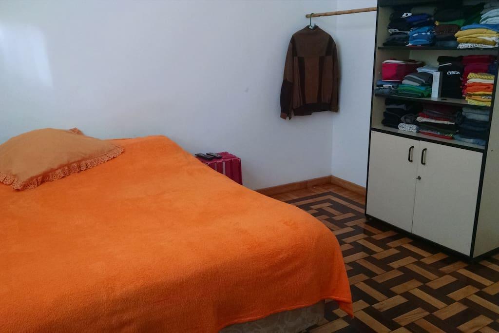 Quarto grande com cama de casal, armário para roupas, TV grande com canais a cabo