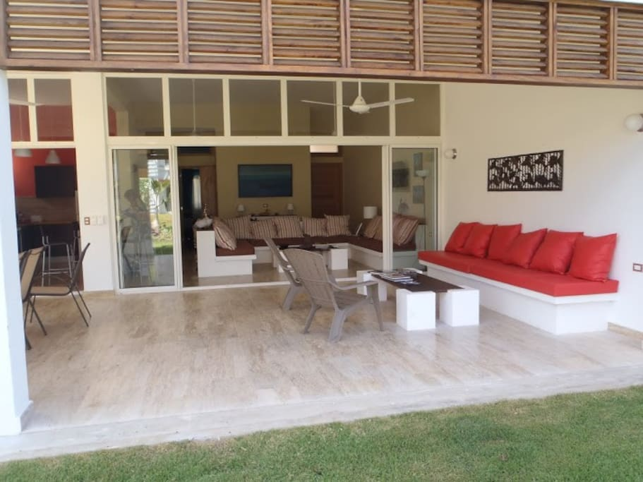 The outside living room and dining room in front of the tropical garden and seaside