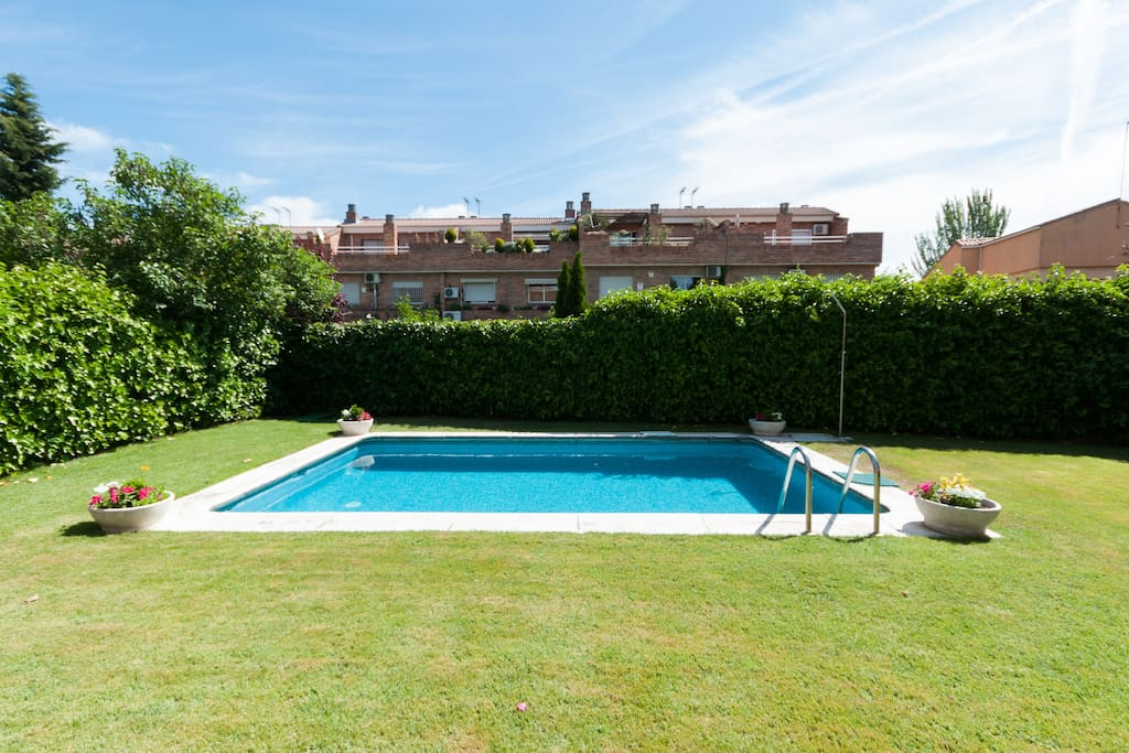 Amplia piscina con césped natural