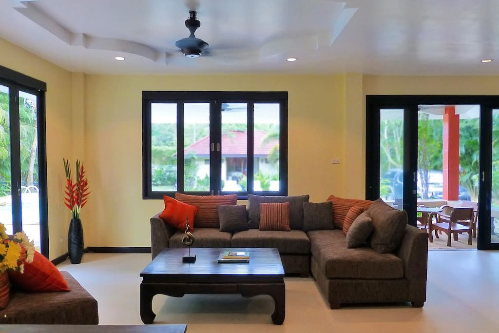 Relax in the spacious living room with  comfortable sofa opening out onto the terrace overlooking the pool.