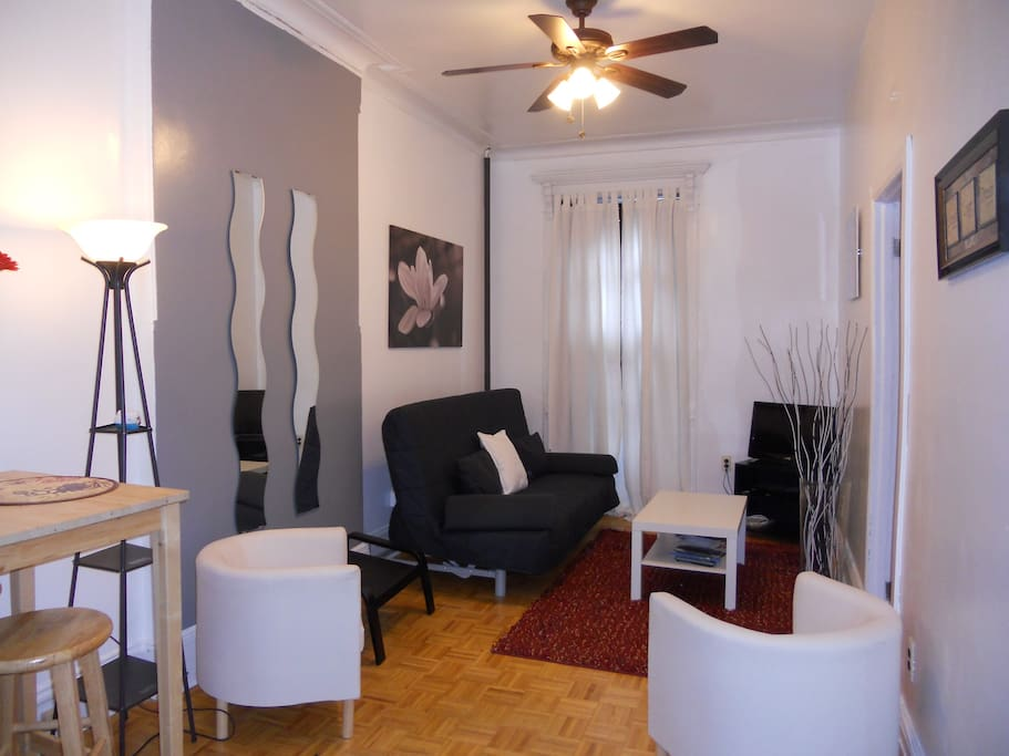 Living room with 2 side chairs,and futon which can turn into a full size bed, 2 end chairs, flat screen TV, WIFI, lots of natural light, not forgetting ceiling fan, & AC.