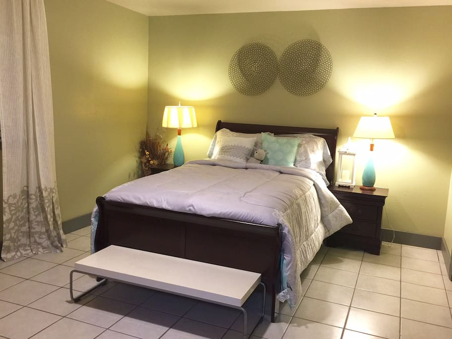 Queen sized bed with convenient lamps and night stands.  Bedroom also has plenty of storage spaces for clothing and dressing area.