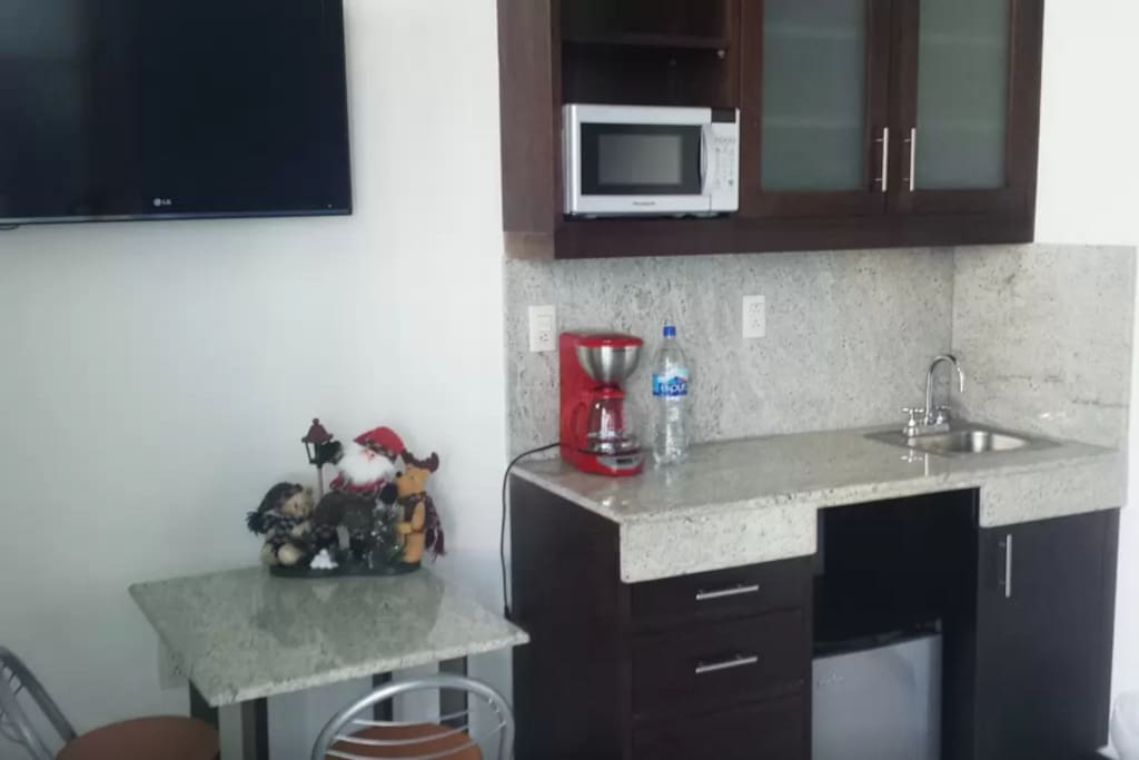 Kitchen includes a small table, satellite tv, microwave, coffe maker, plateware and mini bar.