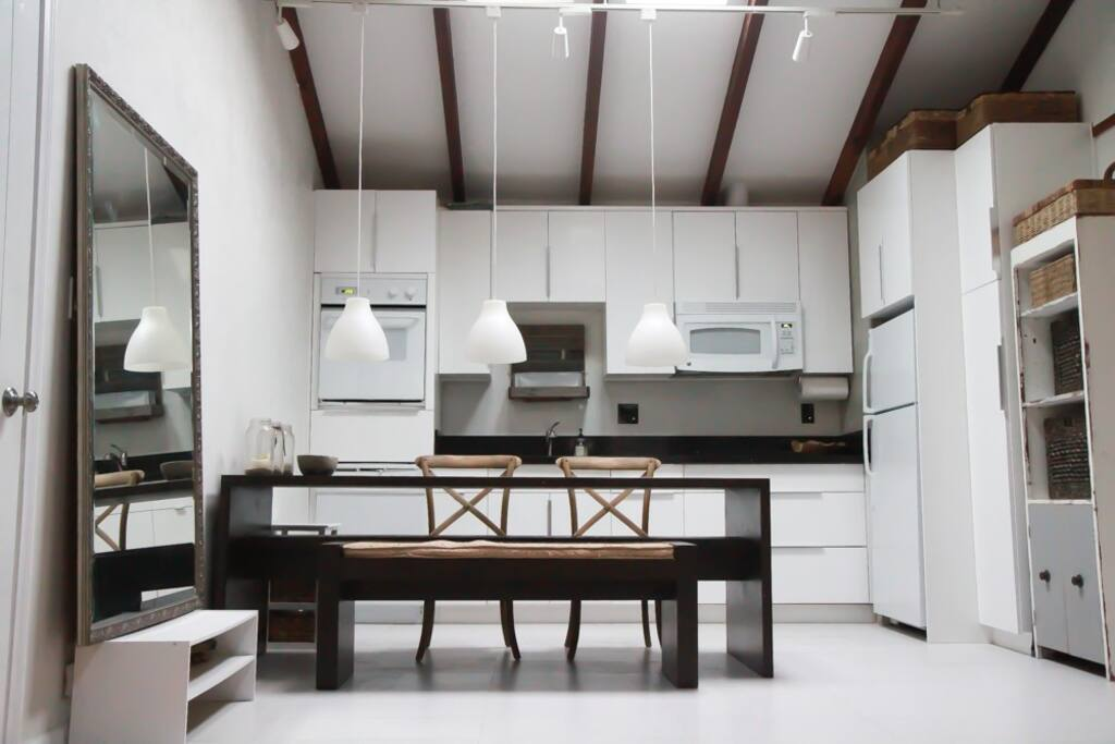 Open concept kitchen features vaulted ceilings, a custom wood dining table, and ample seating