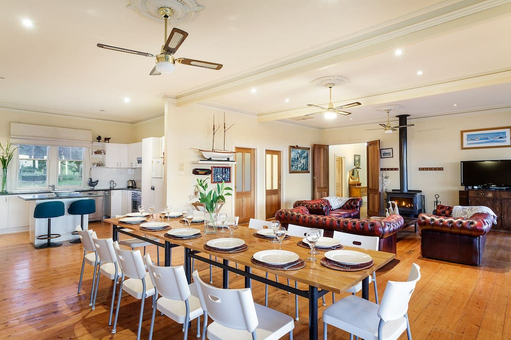 Main kitchen, dining table and lounge with wood heater & ceiling fans