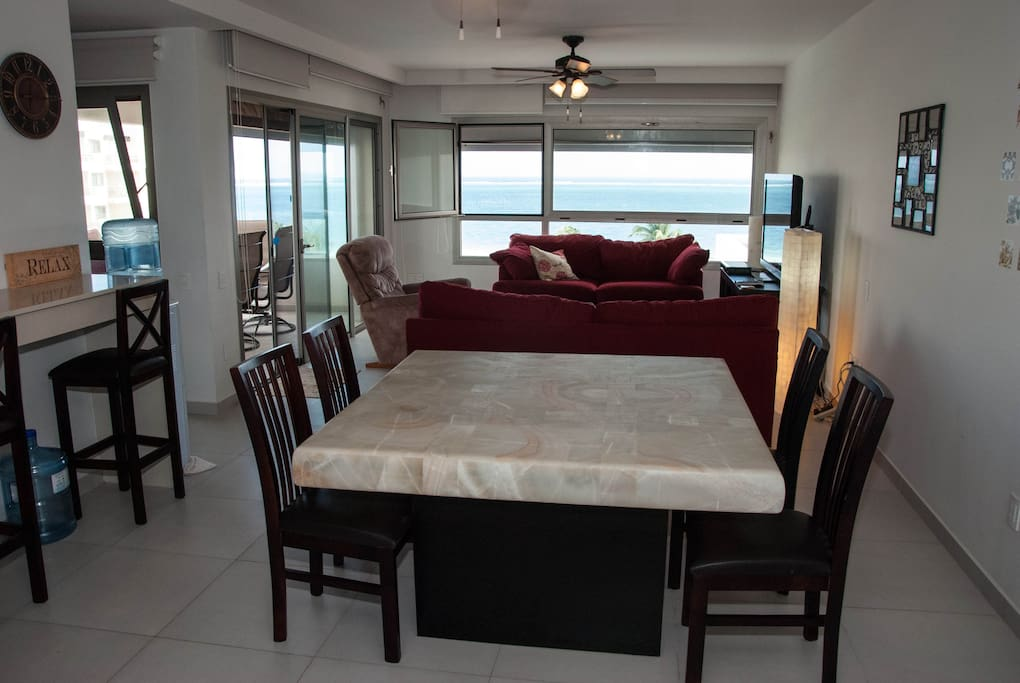 Open concept living area with a view to the ocean and terrace access.  Luxuriously furnished with quality, comfortable couches and chairs.
