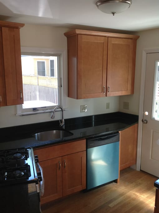 Granite counters, oak cabinets, and modern appliances in kitchen