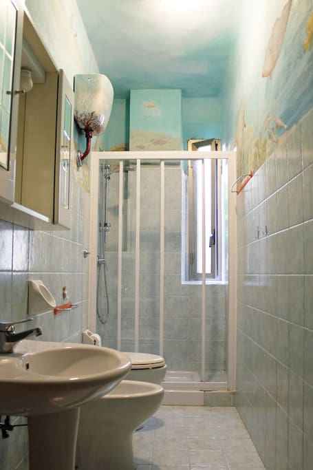 Bathroom with shower and sea-themed paintings on the wall