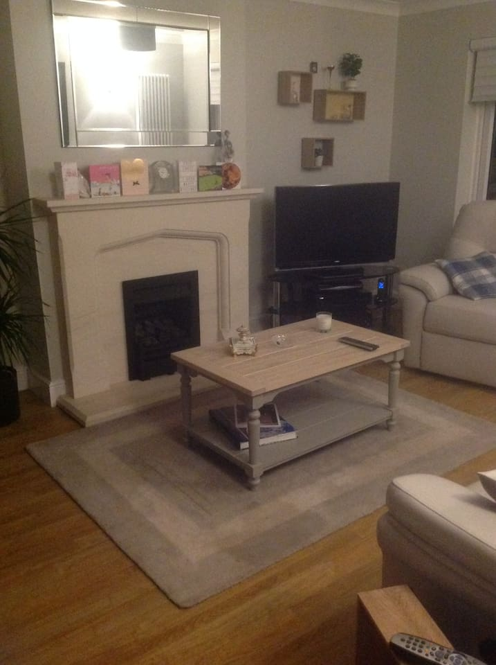 Large lounge with gas fire tv and leading into conservatory
