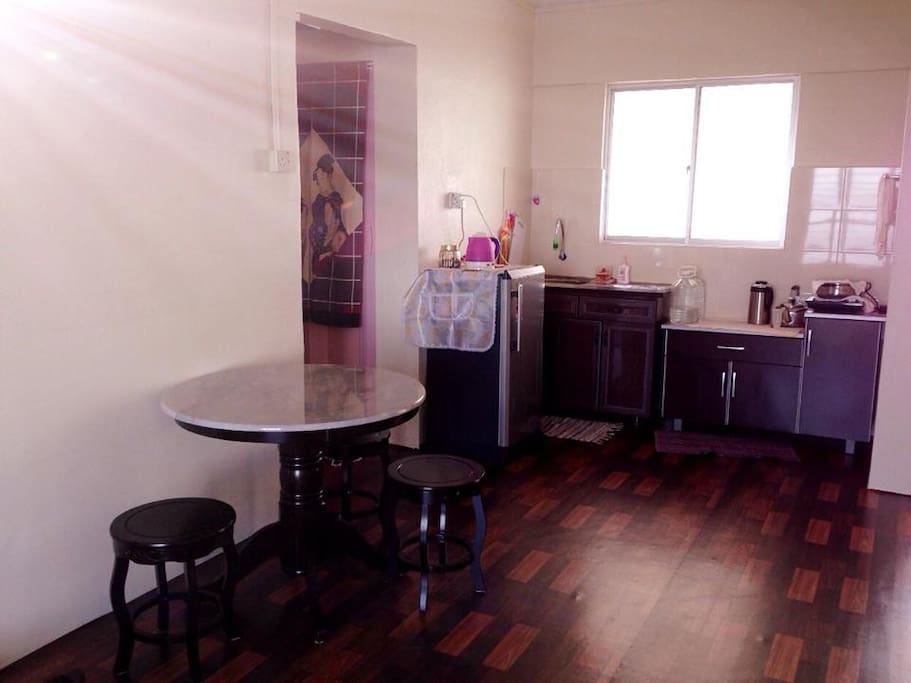 There are dining table, refrigerator, washing machine, and kitchen
