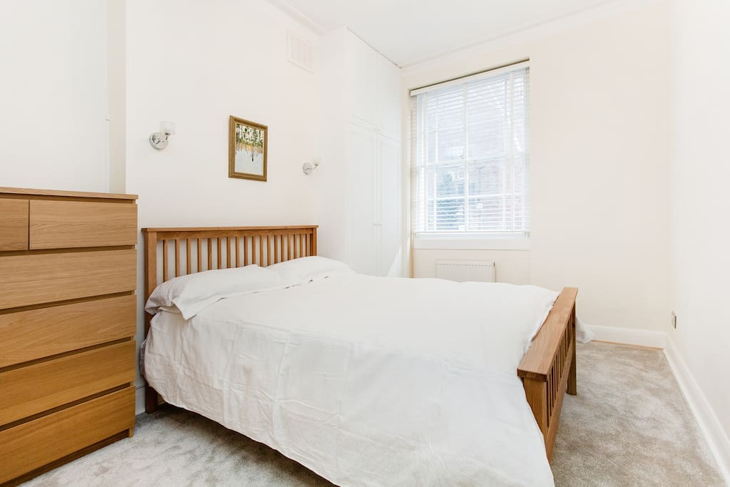 Master bedroom with double bed, reading lights and ample storage.