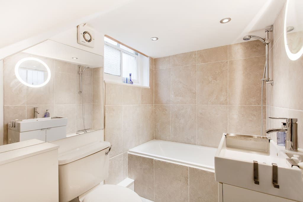 Clean, modern bathroom with washing machine/dryer and hot shower over bath.
