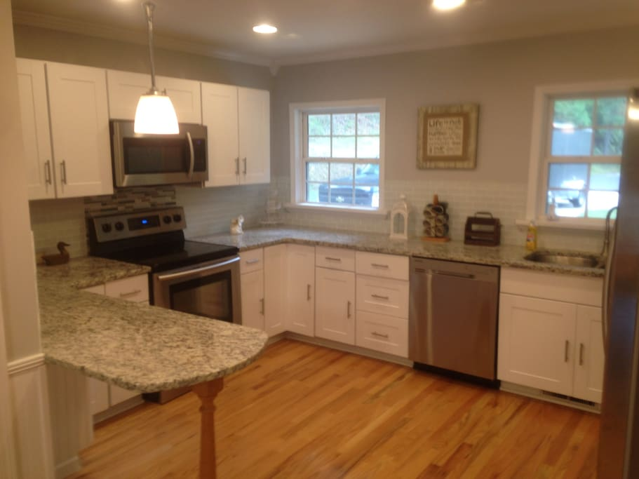 Large kitchen with new granite, white shaker cabinets  and appliances