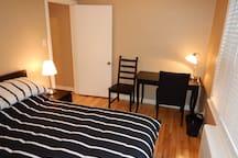 La chambre secondaire est complétée par un bureau de travail et une table de nuit.