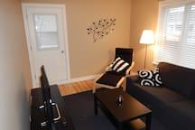 Le salon est spacieux et meublé avec goût. La porte conduit au balcon.