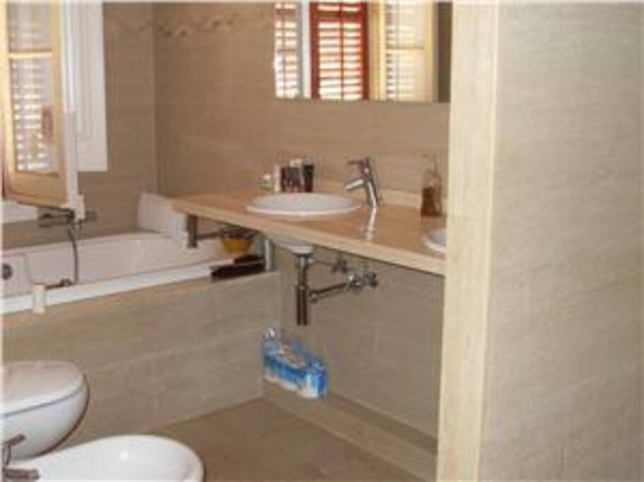 Large bright and airy bathroom with dual sink, shower and bidet.