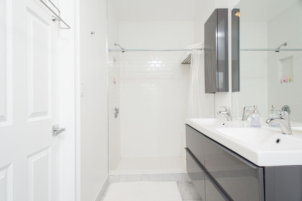Private en suite bathroom with dual sinks, walk in shower with subway tiled built in bench. Clean modern design.